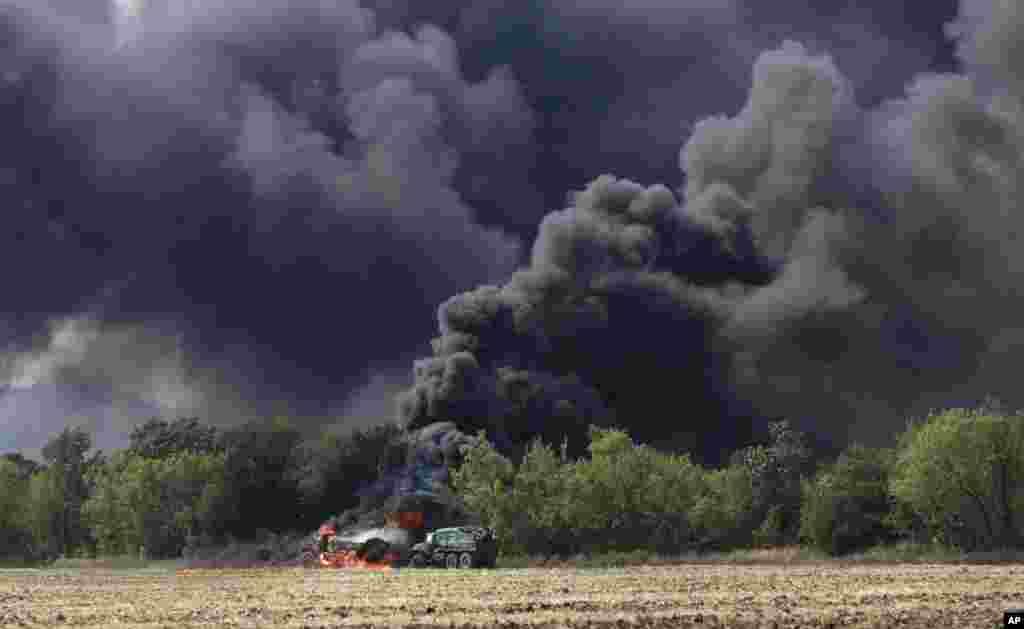 Xe quân sự bốc cháy trên một con đường ở làng Berezove, phía đông Ukraine, sau một cuộc đụng độ giữa quân đội chính phủ và quân ly khai thân Nga.