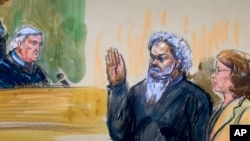 This artist's rendering shows United States Magistrate, Judge John Facciola, swearing in the defendant, Libyan militant Ahmed Abu Khatallah, wearing a headphone, as his attorney Michelle Peterson looks on during a hearing at the federal U.S. District Cour