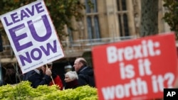 Pro and anti Brexit protesters hold placards as they vie for media attention near Parliament in London, Nov. 16, 2018. Britain's Prime Minister May still faces the threat of a no-confidence vote, after several Conservative Party lawmakers said they had wr