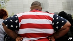 FILE - In this May 8, 2014 photo, an overweight man wears a shirt patterned after the American flag during a visit to the World Trade Center, in New York.