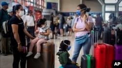 Turis mengenakan masker penutup wajah di Bandara Internasional Havana, Kuba, 23 Maret 2020.