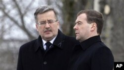 Poland's President Bronislaw Komorowski (l) and Russia's President Dmitry Medvedev during a ceremony marking the one-year anniversary of the Polish presidential plane crash at the crash site near Smolensk, western Russia, April 11, 2011