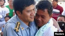 Một giới chức kiểm ngư chào đón ngư dân đảo Lý Sơn, chủ nhân của chiếc thuyền bị tàu của Trung Quốc đâm chìm gần quần đảo tranh chấp Hoàng Sa, trở về nhà.