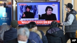 People watch a TV screen showing images of South Korean director Bong Joon Ho during a news program at the Seoul Railway Station in Seoul, South Korea, Monday, Feb. 10, 2020.
