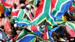 South African football fans wave national flags at one of their team's World Cup warm-up games.....National pride is evident all over the host country in the build-up to the soccer showpiece