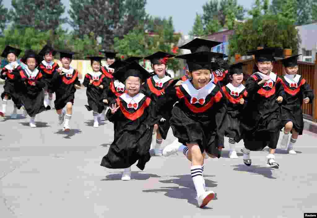 河北邯郸一所幼儿园的小朋友们穿学袍参加毕业典礼(2017年6月20日)