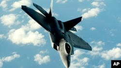 FILE - This U.S. Air Force photo shows an F-22A Raptor returning to a mission after receiving fuel from a KC-135T Stratotanker aircraft Jan. 23, 2009, at Kadena Air Base in Japan.
