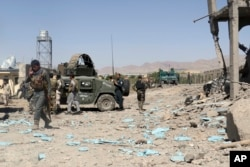 FILE - In this June. 18, 2017, photo, security forces are deployed to the site of a suicide attack between Taliban insurgents and government forces near the main police station in eastern Paktia province, Afghanistan.