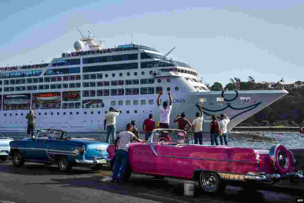Cubans watch as the first U.S.-to-Cuba cruise ship glides into the port of Havana.