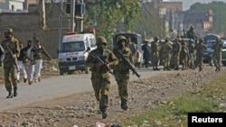 Binh sĩ Pakistan chạy về hướng sân bay Peshawar sau vụ tấn công, ngày 16/12/2012.
