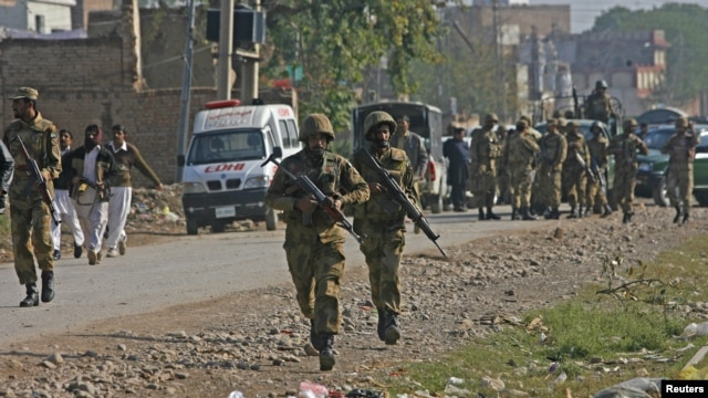 Pakistani army soldiers run towards a gun battle with Taliban militants near Peshawar's airport, December 16, 2012.