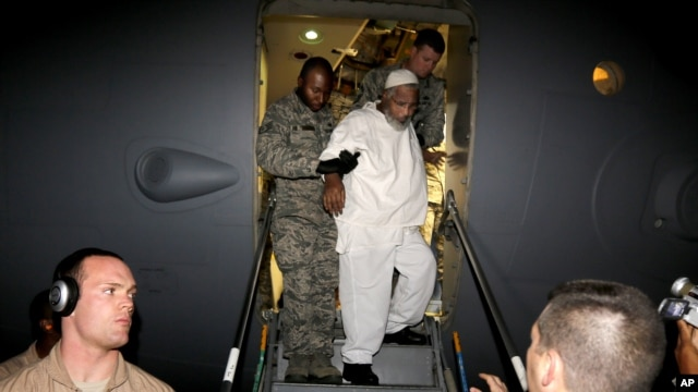 Ibrahim Idris, is escorted off a U.S. military plane by  after his release from Guantanamo Bay, upon his arrival at the airport in Khartoum, Sudan, Thursday, Dec. 19, 2013  (AP Photo/Abd Raouf)