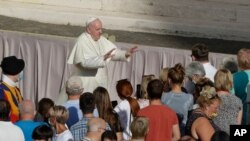 Pope Francis asks the faithful to keep safety distance as he arrives during his weekly general audience in San Damaso courtyard at the Vatican, Wednesday, Sept. 9, 2020. (AP Photo/Andrew Medichini)