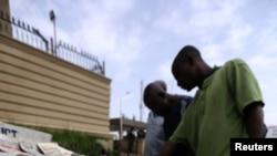 Pedestrians look at newspapers in Abuja, Nigeria on June 5, 2021.
