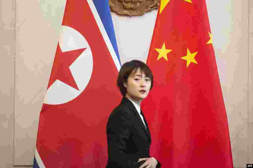 2018年12月7日,在朝鲜外相李勇浩与中国外交部长王毅在北京钓鱼台国宾馆会晤前,一名服务员走过朝鲜和中国国旗。