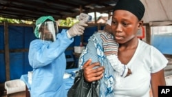 A woman has her temperature taken as part of Ebola prevention, prior to entering the Macauley government hospital in Freetown, Sierra Leone, Jan. 21, 2016.