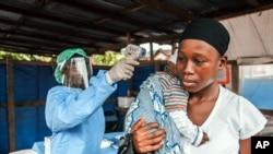 ARCHIVES - Une femme se fait prendre la température dans le cadre de la prévention d'Ebola, à l'entrée de l'hôpital public Macauley à Freetown, Sierra Leone, le 21 janvier 2016.