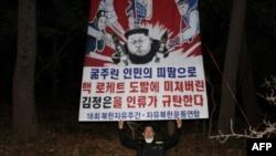 Park Sang-hak melepaskan spanduk bergambar kartun Pemimpin Korea Utara Kim Jong-un yang terpasang pada balon, di lokasi yang dirahasiakan dekat zona demiliterisasi (DMZ) yang memisahkan Korut dengan Korsel, 30 April 2021. (Foto: Handout / Fighters for a Free North Korea / AFP)