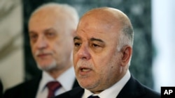FILE - Iraqi Prime Minister Haider al-Abadi, right, holds a new conference before leaving to the United States at Baghdad airport, April 13, 2015.