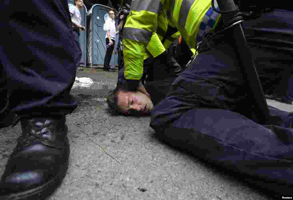 Police detain an anti-fracking demonstrator outside a drill site run by Cuadrilla Resources, near Balcombe in southern England.