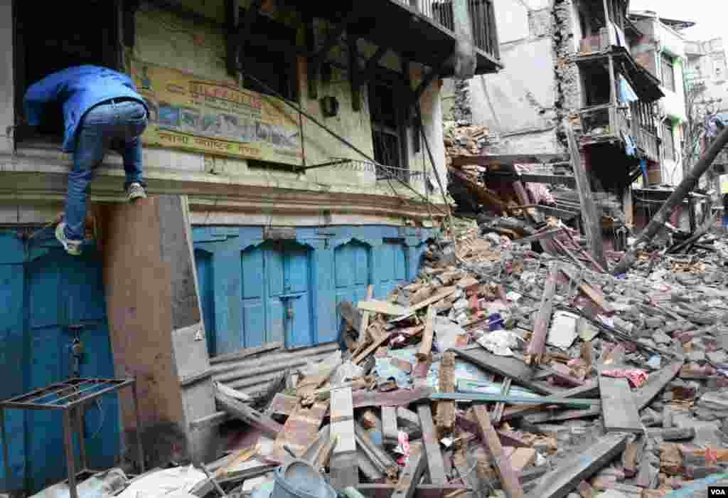 A man exits his home through the window after removing some of his property, Tyouda, Asan, Kathmandu, April 27, 2015. (Bikas Rauniar/VOA)