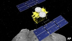 This computer graphics image released by the Japan Aerospace Exploration Agency (JAXA) shows the Hayabusa2 spacecraft above the asteroid Ryugu. (ISAS/JAXA via AP)
