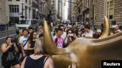 Les touristes posent devant le célèbre taureau de Wall Street à New York , le 24 août 2015.
