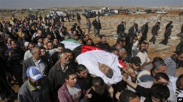 Mourners carry the body of Khairi Saad, 55, who died in the anti-government protests, at the Islamic cemetery in Sahab, near Amman, in Jordan, March 27, 2011