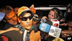Rescued miner Carlos Mamani, from Bolivia, is surrounded by the press as he arrives to his home in Copiapo, Chile, 14 Oct. 2010