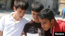 시리아 알레포의 반군 점령지역에 거주하는 청소년들이 28일 반군의 투항을 촉구하는 내용의 정부군 선전물을 읽고 있다.