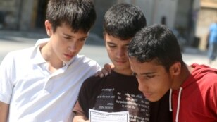 Boys read a leaflet dropped by the Syrian army over opposition-held Aleppo districts asking residents to cooperate with the military and calling on fighters to surrender, July 28, 2016.