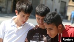 FILE - Boys read a leaflet dropped by the Syrian army over opposition-held Aleppo districts asking residents to cooperate with the military and calling on fighters to surrender, July 28, 2016.