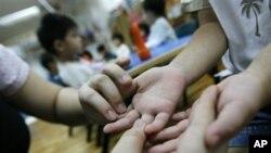 Guru di taman kanak-kanak di Singapura ini memeriksa kemungkinan adanya bintik-bintik dan kulit melepuh, gejala penyakit tangan, kaki, dan mulut, pada tangan anak-anak (foto: dok.).