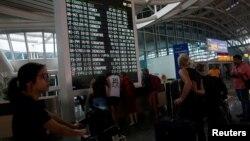 Para penumpang berkerumun di depan papan informasi penerbangan di Bandara Internasional Ngurah Rai di Denpasar, setelah pejabat berwenang menngkatkan status keamanan penerbangan menyusul erupsi Gunung Agung, 26 November 2017.