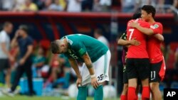 Germany's Niklas Suele, left, is dejected as South Korea's Son Heung-min, right, celebrates after the group F match between South Korea and Germany, at the 2018 soccer World Cup in the Kazan Arena in Kazan, Russia, Wednesday, June 27, 2018. (AP Photo/Frank Augstein)