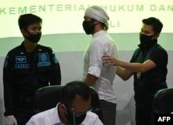 Instruktur yoga Wissam Barakeh (tengah) dari Suriah ditangkap oleh petugas Imigrasi sebelum konferensi pers di Rumah Detensi Imigrasi di Jimbaran, Bali, 24 Juni 2020. (Foto: dok).