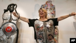 In this July 10, 2014 photo, a woman strikes a power pose after putting on a piece of wearable art by Linda Stein. This piece has a Wonder Woman theme designed to give the wearer a sense of empowerment.(FILE PHOTO)