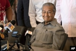 FILE - Mahathir Mohamad smiles during a press conference in Kuala Lumpur, Malaysia, May 10, 2018.