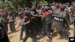 Police officers beat a student protester after detaining him following a crackdown in Letpadan, 140 kilometers (90 miles) north of the country's main city Yangon, Myanmar, Tuesday, March 10, 2015.
