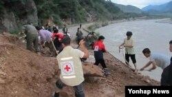 지난달 24일 평안남도 신양군 수해피해 현장을 복구하는 적십자 회원들.