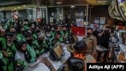 Pengemudi pengiriman makanan mengantre di gerai McDonald's di Bogor pada 9 Juni 2021. Mereka membeli paket meal BTS, menyebabkan lebih dari selusin gerai McDonald's tutup sementara karena ketakutan perebakan virus corona. (Foto: AFP/Aditya Aji)