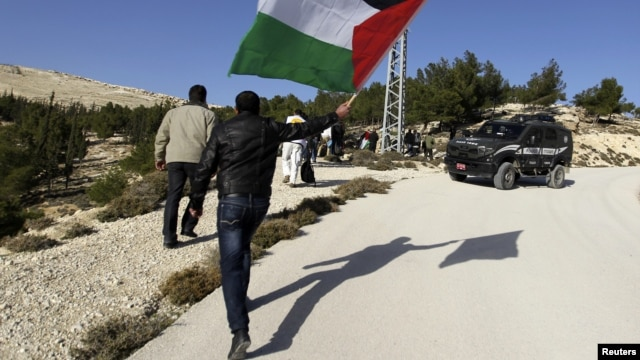 A Palestinian protester holds a flag as he arrives at an area known as 'E1', which connects the two parts of the Israeli-occupied West Bank outside Arab suburbs of East Jerusalem, January 15, 2013.