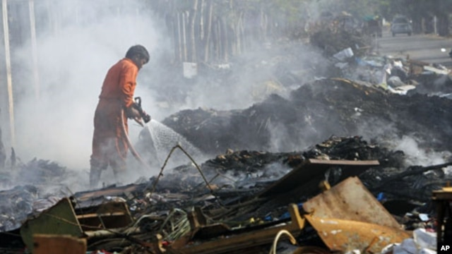 A firefighter puts out a fire on a pile debris left behind after flood waters, one of Thailand's worst floods in five decades, receded in Bangkok, January 6, 2012.