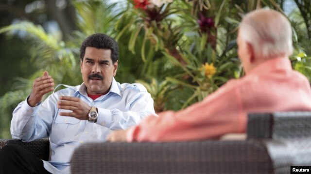 Venezuela's acting President Nicolas Maduro (L) speaks during an interview in Caracas, March 16, 2013, in this handout photo provided by the Miraflores Palace.