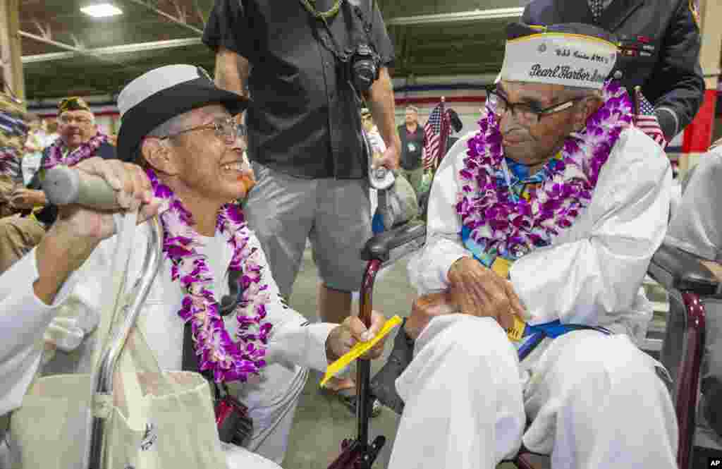 Kathleen Chavez, left, talks with her father Ray Chavez, right, age 104, of the USS Condor. The oldest living survivor from the Pearl Harbor attacks along with the remaining living survivors of the USS Arizona gathered at the World War II Valor in the Pacific National Monument at Joint Base Pearl Harbor-Hickam, in Honolulu, Hawaii.