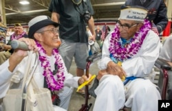 Kathleen Chavez, left, talks with her father, Ray Chavez, age 104, of the USS Condor, the oldest living survivor from the Pearl Harbor attacks, along with the remaining living survivors of the USS Arizona gathered at the World War II Valor in the Pacific National Monument at Joint Base Pearl Harbor-Hickam in Honolulu, Dec. 7, 2016.