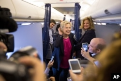 FILE - Democratic presidential candidate Hillary Clinton, accompanied by traveling press secretary Nick Merrill, left, and director of communications Jennifer Palmieri, right, listens to a question from a member of the media on her campaign plane.