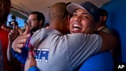 St. Louis Cardinals player Brayan Pena, from Cuba, embraces a former colleague before giving a baseball clinic to children in Havana, Cuba, Dec. 16, 2015.