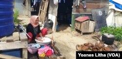 Nurjanah, 29, mencuci pakaian di luar tenda sambil memasak air minum untuk kebutuhan keluarganya, Selasa, 18 Juni 2019. (Foto:Yoanes Litha/VOA)