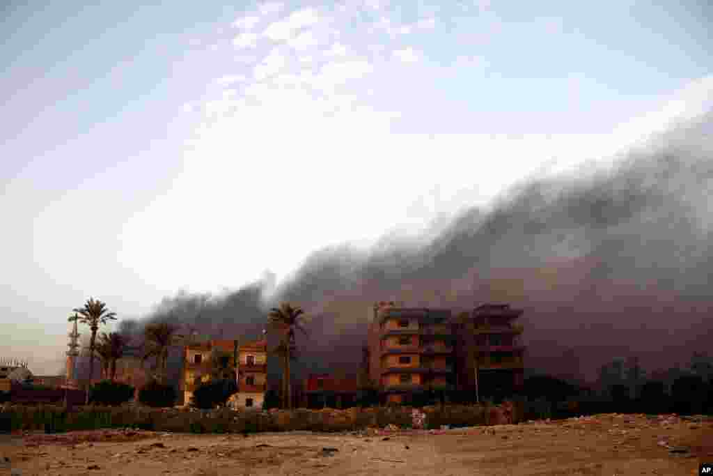 Smoke rises during clashes between Egyptian security forces and suspected militants in the town of Kirdasah, near Giza Pyramids.